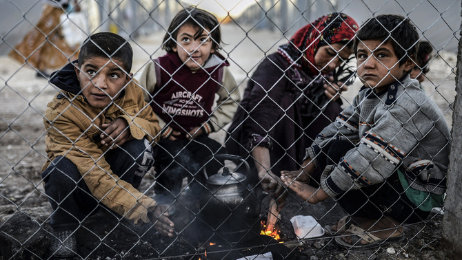Syrian Kurdish woman and her children gather around a fire early in the morning in a refugee camp at Suruc, in the Sanliurfa province, on October 21, 2014. Turkey dropped its refusal to allow Kurdish fighters over the border to defend the besieged Syrian town of Kobane, saying it was now helping Iraqi peshmerga to cross the frontier in a major policy shift. AFP PHOTO / BULENT KILIC TURKEY-SYRIA-CONFLICT-KURDS